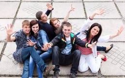 Allievi del gruppo che si siedono sulla via Fotografia Stock Libera da Diritti