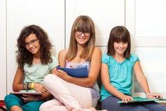 Allievi dell'adolescente che si siedono con gli archivi. Immagine Stock