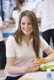 Allievi della High School che mangiano nel banco Immagine Stock