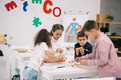 Allievi della scuola elementare che lavorano con i modelli molecolari alla classe di chimica Immagine Stock