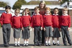 Allievi della scuola elementare con l'insegnante In Playground Immagine Stock