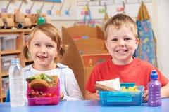 Allievi della scuola elementare con le scatole di pranzo sane e non sane Immagine Stock