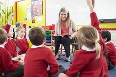 Allievi della scuola elementare di Reading Story To dell'insegnante Immagini Stock
