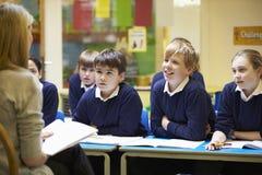 Allievi della scuola elementare di Teaching Lesson To dell'insegnante Immagine Stock