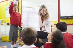 Allievi della scuola elementare di Teaching Maths To dell'insegnante Fotografie Stock