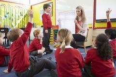 Allievi della scuola elementare di Teaching Maths To dell'insegnante Immagini Stock
