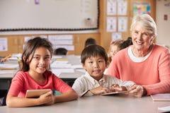 Allievi della scuola elementare e dell'insegnante senior in aula Fotografia Stock