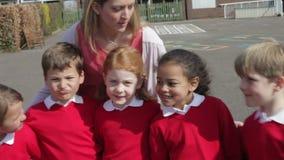 Allievi della scuola elementare ed insegnante In Playground video d archivio