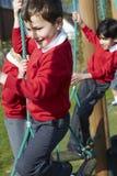 Allievi della scuola elementare su attrezzatura rampicante Immagini Stock