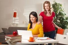Allievi di Highschool che esaminano computer portatile Immagine Stock