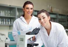 Allievi di scienza che propongono con un microspcope Fotografia Stock