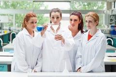Allievi di scienza che versano liquido in una boccetta Fotografie Stock