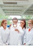 Allievi di scienza che versano liquido in una boccetta Fotografia Stock
