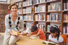 Allievi e lettura svegli dell'insegnante nella biblioteca Fotografia Stock