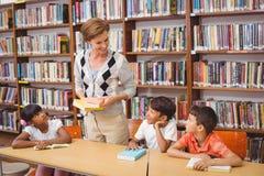 Allievi e lettura svegli dell'insegnante nella biblioteca Fotografie Stock Libere da Diritti