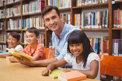 Allievi e lettura svegli dell'insegnante nella biblioteca Immagini Stock
