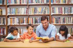 Allievi e lettura svegli dell'insegnante nella biblioteca Immagini Stock Libere da Diritti