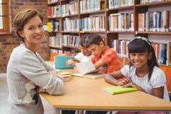 Allievi e lettura svegli dell'insegnante nella biblioteca Fotografie Stock