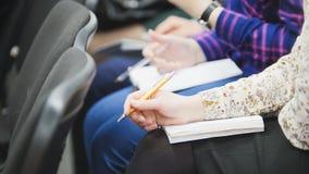 Allievi e studenti - ascoltando alla conferenza o alla presentazione, officina, classe matrice - note e penne Fotografia Stock