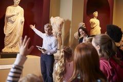 Allievi e viaggio di On School Field dell'insegnante al museo con la guida Immagine Stock