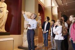 Allievi e viaggio di On School Field dell'insegnante al museo con la guida Fotografie Stock Libere da Diritti