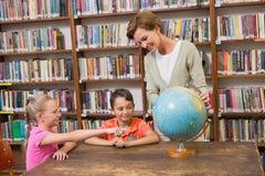 Allievi ed insegnante che esaminano globo in biblioteca Immagine Stock Libera da Diritti