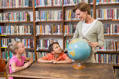 Allievi ed insegnante che esaminano globo in biblioteca Immagini Stock