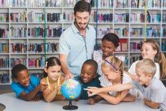 Allievi ed insegnante che esaminano globo in biblioteca Fotografia Stock