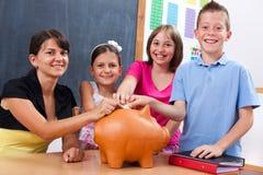 Allievi ed insegnante che mettono moneta nella banca piggy Immagini Stock Libere da Diritti