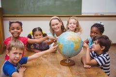 Allievi ed insegnante svegli in aula con il globo Immagini Stock