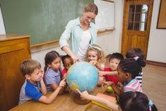 Allievi ed insegnante svegli in aula con il globo Fotografie Stock