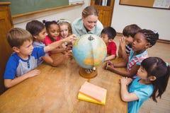 Allievi ed insegnante svegli in aula con il globo Fotografia Stock