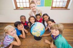 Allievi ed insegnante svegli in aula con il globo Fotografia Stock Libera da Diritti