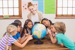 Allievi ed insegnante svegli in aula con il globo Fotografie Stock Libere da Diritti