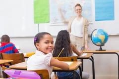 Allievi ed insegnante svegli in aula con il globo Immagine Stock