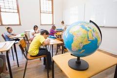 Allievi ed insegnante svegli in aula con il globo Immagini Stock Libere da Diritti