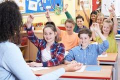 Allievi elementari che rispondono alla domanda nella classe Immagini Stock Libere da Diritti