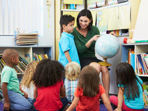 Allievi elementari nella classe di geografia con l'insegnante Fotografia Stock