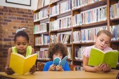 Allievi felici che leggono un libro delle biblioteche Fotografia Stock