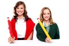 Allievi femminili che scrivono con la grande matita Fotografia Stock