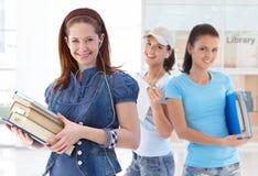 Allievi femminili felici nell'ingresso delle biblioteche Fotografie Stock Libere da Diritti