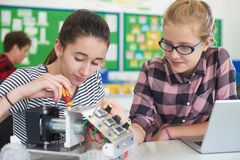 Allievi femminili nella lezione di scienza che studiano robotica Immagini Stock
