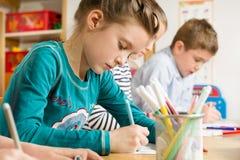 Allievi minori che disegnano con gli evidenziatori Immagini Stock