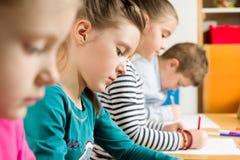 Allievi minori che disegnano con gli evidenziatori Immagine Stock