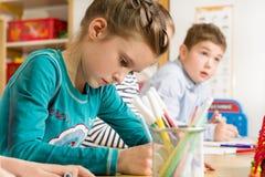 Allievi minori che disegnano con gli evidenziatori Immagini Stock Libere da Diritti
