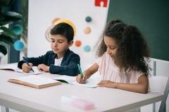 Allievi multietnici che scrivono esercizio alla lezione nella classe Fotografia Stock