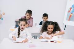 Allievi multietnici sorridenti che studiano con i manuali in aula Immagini Stock