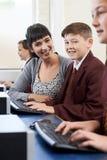 Allievi nella classe del computer con l'insegnante Immagini Stock
