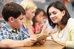 Allievi nella classe facendo uso della compressa di Digital con l'insegnante Immagini Stock