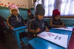 Allievi nella classe inglese alla scuola primaria Soltanto 50% dei bambini nel Nepal può raggiungere il grado 5 Immagine Stock